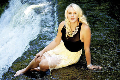 Musician portrait Krista Earle sitting by waterfall in wet white skirt and black blouse