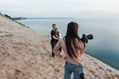 photographer holding camera and looking at man and woman standing next to ocean