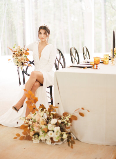 Beautiful bride sits at a reception table holding orange and white bouquet