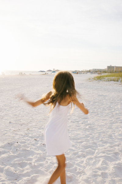young girl twirling at beach session in florida photo by Laurie baker