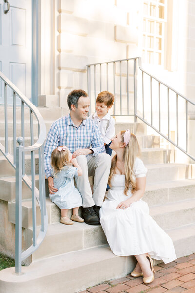 Family sits on steps of Carlyle House during Alexandria family session.