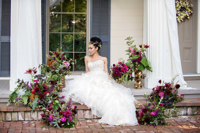 a bride sits on the steps at ainsworth house surrounded by colorful vibrant pink flowers