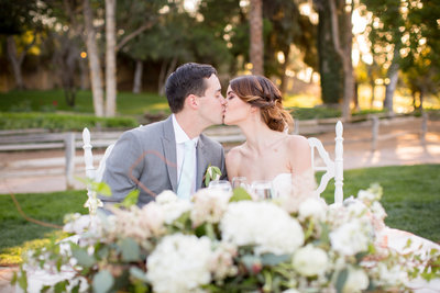 Bride and Groom kissing at head table at Lake Oak Meadows