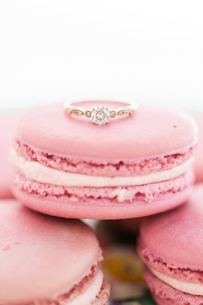Close-up photo of an engagement ring on a pink macaroon for an engagement portrait by Jennifer Marie Studios in Atlanta Georgia.