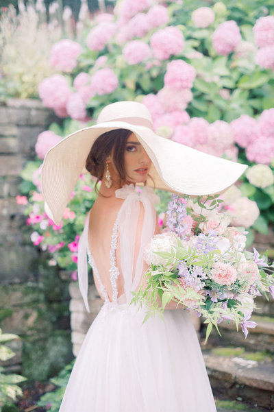 Summer bride with wide brimmed hat holding a bouquet of flowers at Hedsor House