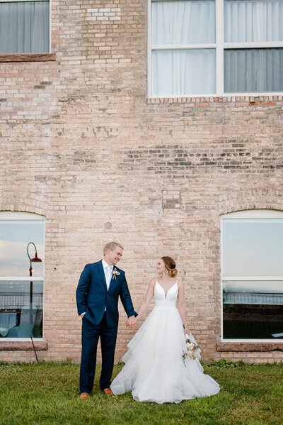 bride & groom holding hands and looking at each other in front of a brick building