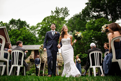 Bride and groom smile triumphantly as they walk down the aisle after being married