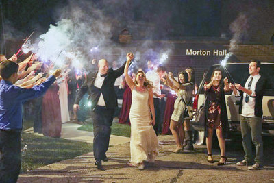 bride and groom exit reception hall to sparklers