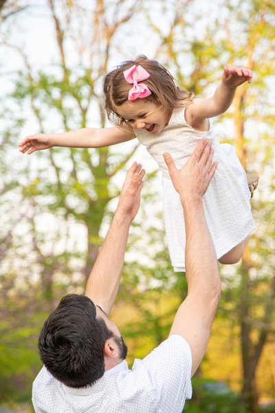 Dad tosses his young daughter in the air as she smiles during family photography session