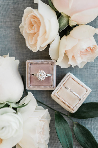 Katie's wedding band and engagement ring on display with florals and greenery