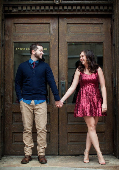 Engagement shoot in Duluth, MN.  Bride is laughing at groom, standing and looking at each other in a vintage doorway.