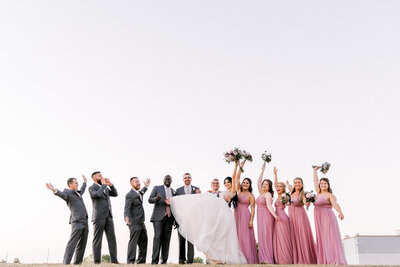 wedding party cheers on a hilltop in Lincoln