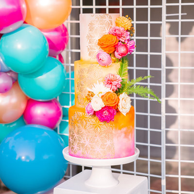 boho wedding cake with flowers and balloon arch