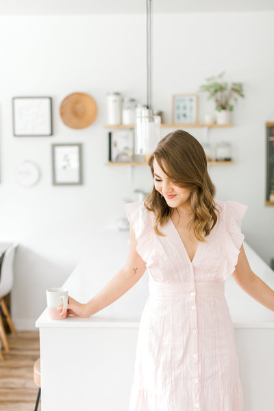 Woman holding coffee cup standing in white kitchen with pink dress