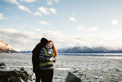 couple embraces surrounded by winter landscape at beluga point