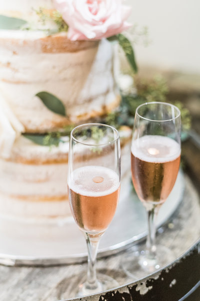 Champagne glasses in front of a beautiful wedding cake.