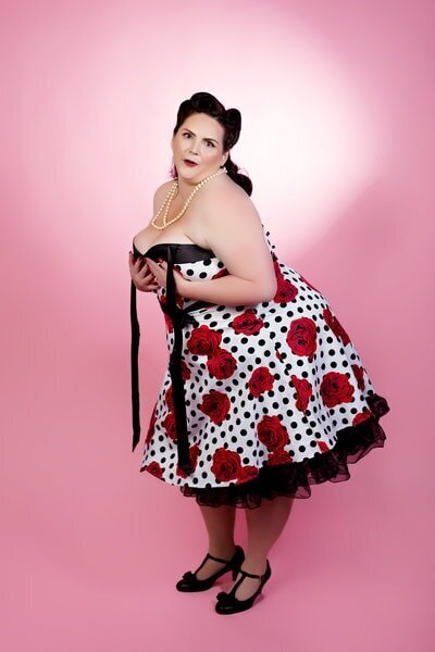 Curvy woman in  polka dot dress with red roses on it, posing for a pinup photo at boudoir and Pinup by Janet Lynn