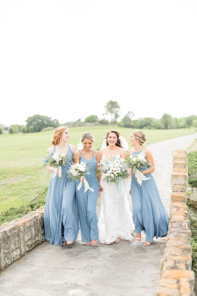 Bride and bridesmaids walk and laugh.
