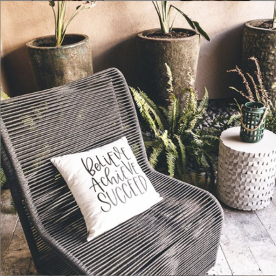 Gray chair outside with pillow on it next to plants