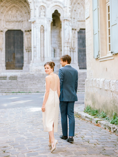 Couple walking on cobblestone streets in France