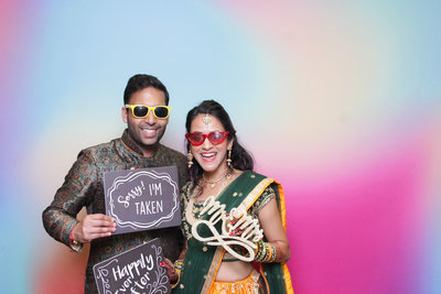 couple holding props front of a colorful backdrop