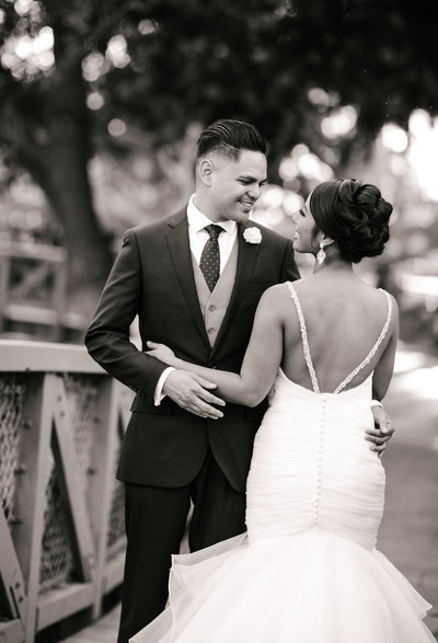 Just married couple embracing outside at their wedding reception, in black and white