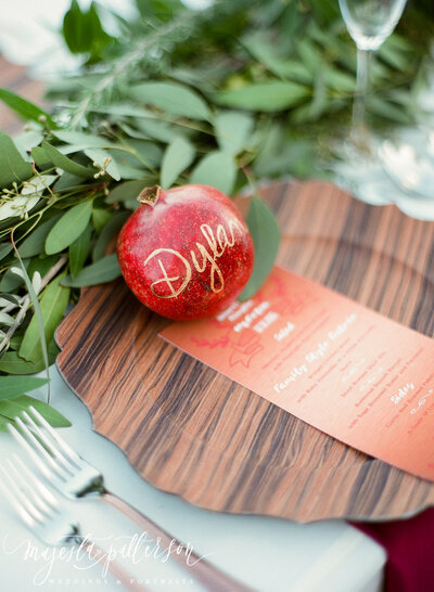 Pomegranate place card with wood and copper details at winery