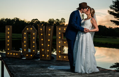 Br5ide and groom kissing next to lighted LOVE sign at sunset during their wedding reception in Waterford, PA