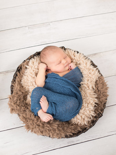 Baby boy wrapped in blue wrap in a round basket on a wooden floor
