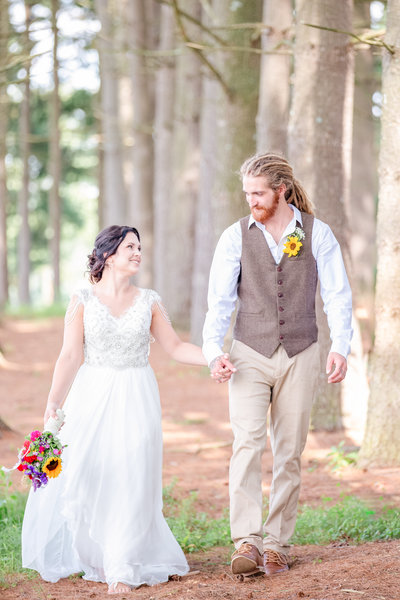 Bride and groom hold hands and smile while walking amidst trees holding bouquet