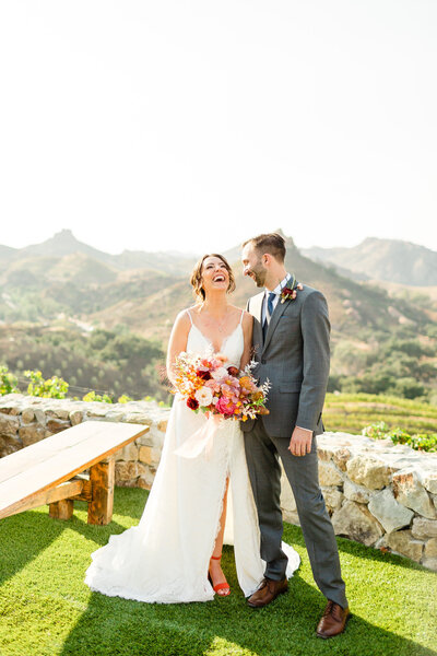 Bride and groom laughing at their Cielo Farms wedding in Malibu, California. Engaged couple kissing in San Francisco, California. Photo taken by Cheers Babe Photo.