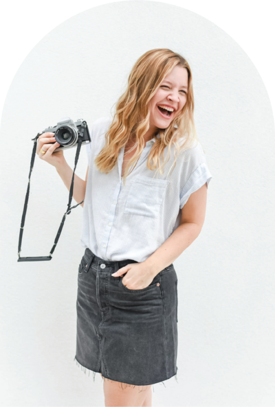 woman smiling holding a camera