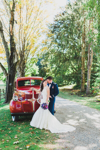 Bride and groom embrace on tree lined path next to vintage red pick up truck