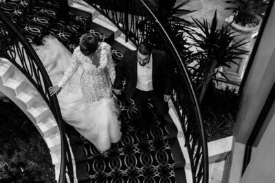 Newlyweds-walking-down-the-stairs-holding-hands-to-their-wedding-car-after-their-reception