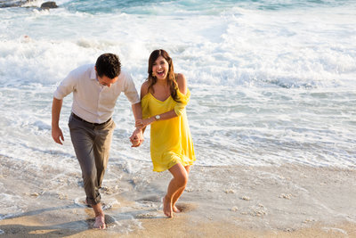 A couple playing in the ocean during their Laguna Beach engagement session.