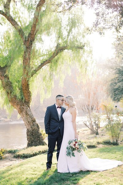 Bakersfield Wedding photographer- Marianne Lucas portrait of a  bride & groom posing nose to nose at the gardens of paradise wedding venue.. Black suit, messy bouquet burgandy, greenery, and blush pinks.