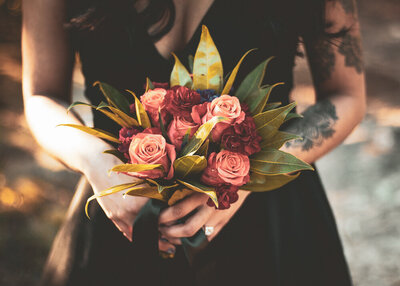 Bride with tattoos and black wedding dress holds bouquet in her Texas elopement.