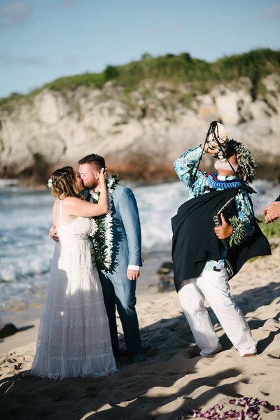 couple kisses on the beach at their destination elopement in hawaii while their officiant blows his conch shell