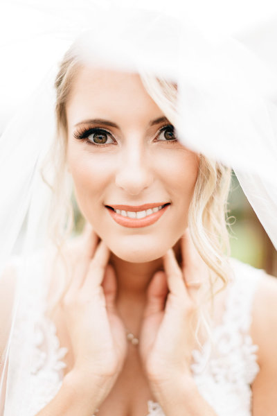 bride smiles as her veil flows around her