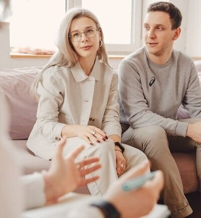 A couple sit next to one another while a person gestures with their hands. This could symbolize what a couples therapist might do during couples communication therapy in Florida. We offer communication therapy for couples in Florida and other services. Contact us today!