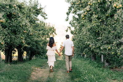 Couple walking through orchard at Beecher Hill House