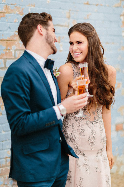 Bride and groom toasting blush wedding dress
