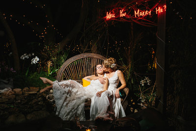 Two Brides sitting together in chair with a kiss on the cheek