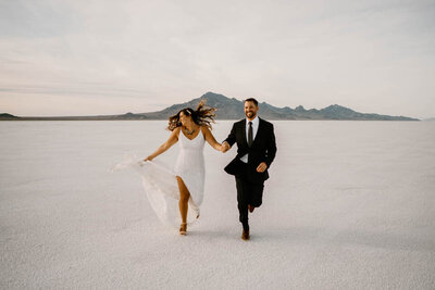 man and woman running in salt flats