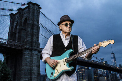 Musician photo Robert Allen standing in front of Brooklyn Bridge wearing sunglasses and black hat while holding blue electric guitar at sunrise