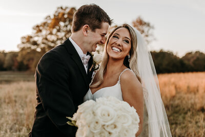 J.Michelle Photography, a photographer in atlanta, ga, captures a bride and groom's laughter at vintage oaks farm wedding in athens, georgia