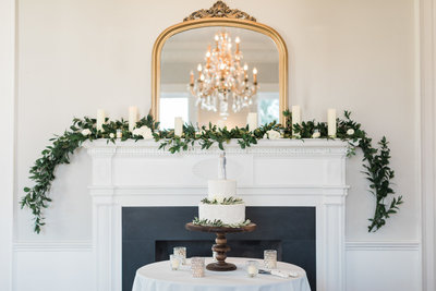 Gadsden House Wedding Cake Table Fireplace Mantle with Greenery and Candles Gold Mirror Charleston Wedding