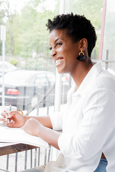 Black woman smilling with a pen in her hand in Washington, DC