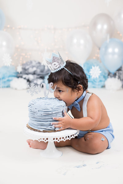 Baby boy eating cake with light blue icing and snowflakes decor