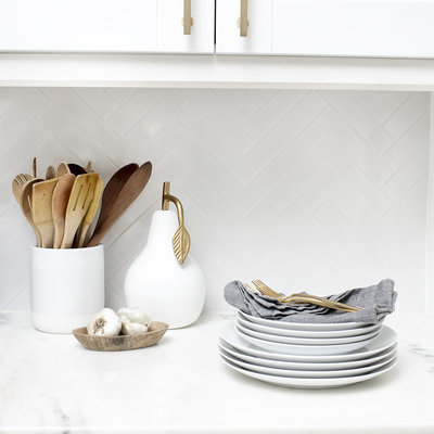 Dishes, napkins, silverware and kitchen accessories on counter in white kitchen